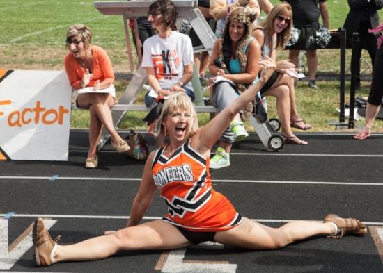 woman in cheerleader clothing doing splits