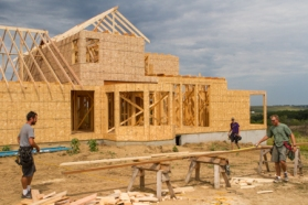 House under construction and carpenters in foreground.