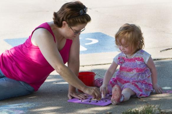 Woman and girl drawing on sidewalk.