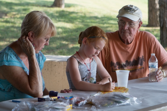 girl and grand parents at picnic table in shelter.
