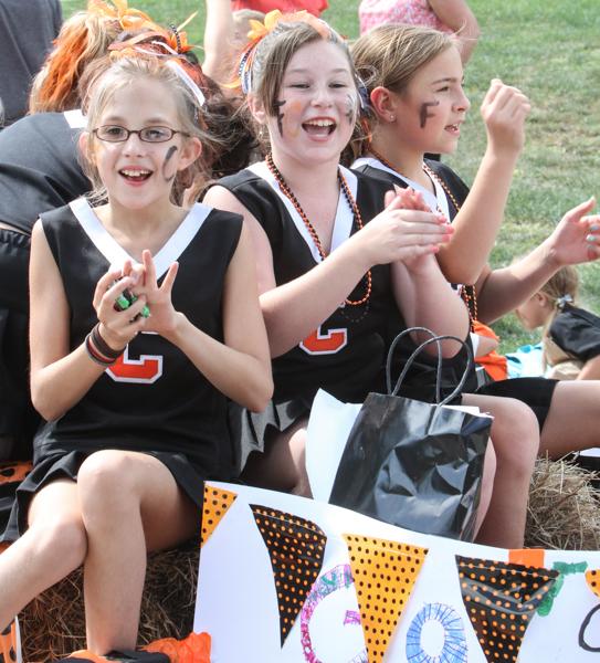 3 girls on trailer dressed as cheerleaders