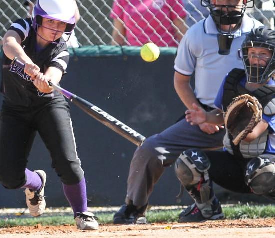 girl at bat hits ball