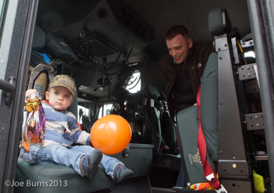 boy sits in seat in firetruck as dad watches.