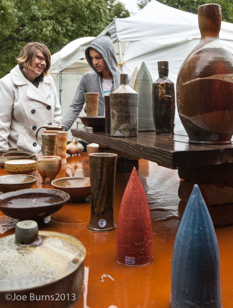 two people looking at table of ceramics.