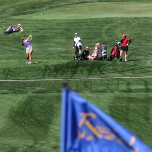 girls tees off while people watch