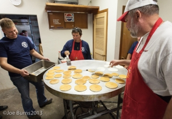 Man with pand waits for pancakes. Two men flip pancakes on griddle