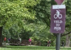 bike yield to peds sign in foreground, boys running in background