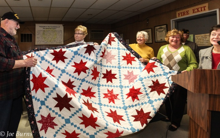 Man and women hold quilt