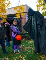 woman and costumed mask and guy in black robe with mask.
