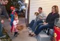 kids and dad visit with 2 people and dog seated on porch