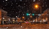 Snow falling on downtown street scene