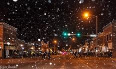Snow falling on downtown street scene