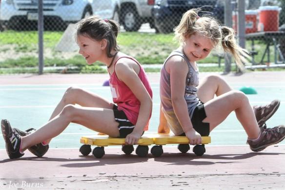 Kendergarteners Allyndra Guerrero and Kaylei Klingforth schoot their way around the tennis courts