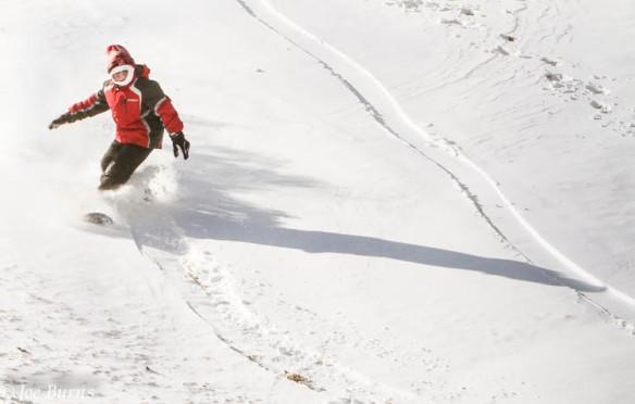 Garret Gibson snowboards down a hill at Ralph Steyer Park.