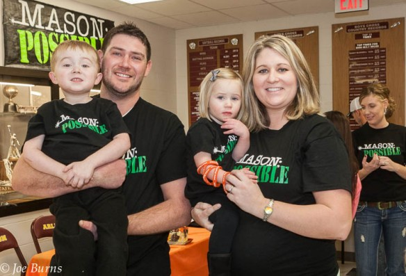 Brandon and Sara Hasenauer hold son Brandon and daughter Holly during the Arlington vs. Wahoo girls basketball game.  Mason was recently diagnosed with a rare kidney disease.