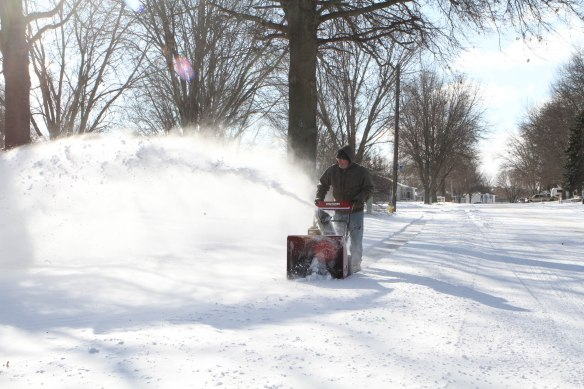 Terry Rasmussen cleans off his  sidwalk along 17th avenue Wednesday morning.