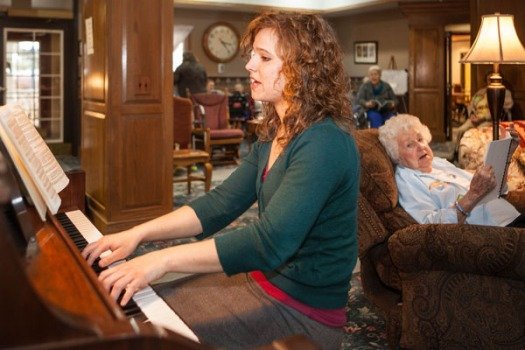 Ellie Stangl plays the piano while Ellenora Plugge listens.