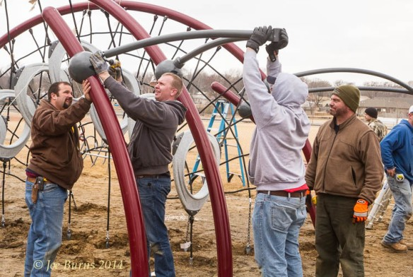 Youth Sports Organization volunteers assemble playground equipment.