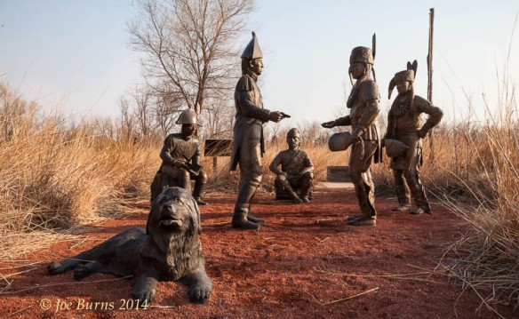 The Meeting Place sculpture by Milt Heinrich is located on the flood plain at the base of the hill on which the fort stockade is located.