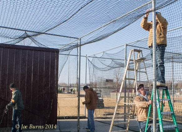 Putting up nets on the batting cages.