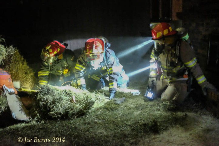Fire fighters Brad Teeger, ty Harness and Ryan Coufal search a dark basement for fire victims during a Firefighting 1 training class.