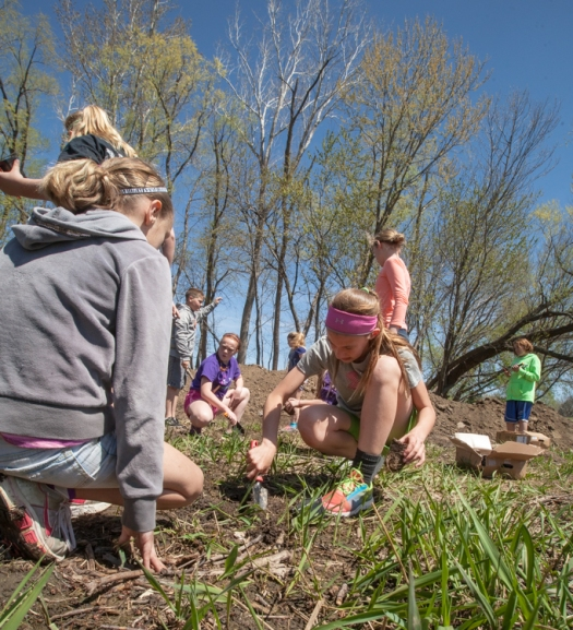 Girls plant along the edge of the wetland area.