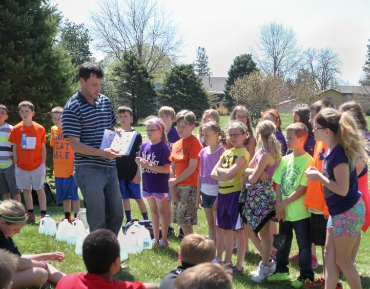 Scott Schmidt shows students a diagram of where the flowers will be planted.