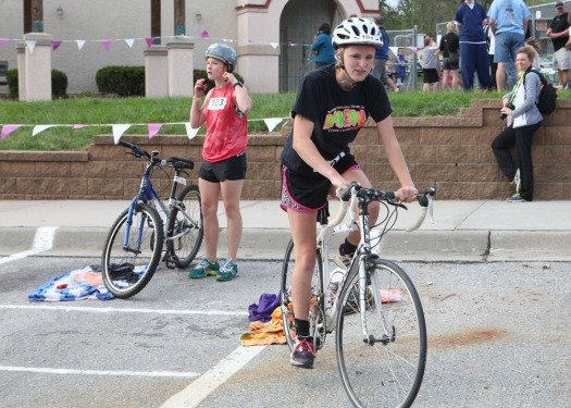 Alex Rand leaves makes the transition area on her bike.