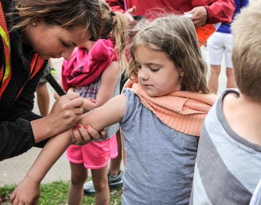 Kendall Kottle gets her arm marked with a number prior tot he start of the triathlon.