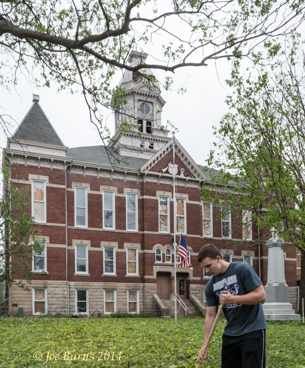 Austin Scherer rakes up debri from the sidewalks at the the badly damaged Washington County Courthouse.