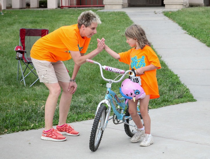 Race organizer Denise Ray gives Olivia Parsons a high five following the triathlon.
