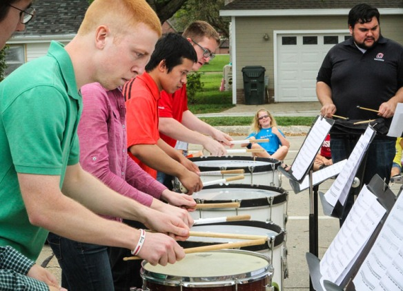 Lizzy Wrightson, background plays air drums while members of the University of of Nebraska Omaha drum line perform Tuesday at the Blair Library. Percussionists, front to back, Philip Kolbo, Amanda Sealock, Raymond Ryan, Zack Besler, and UNO percussion instructor Scott Shinborn.
