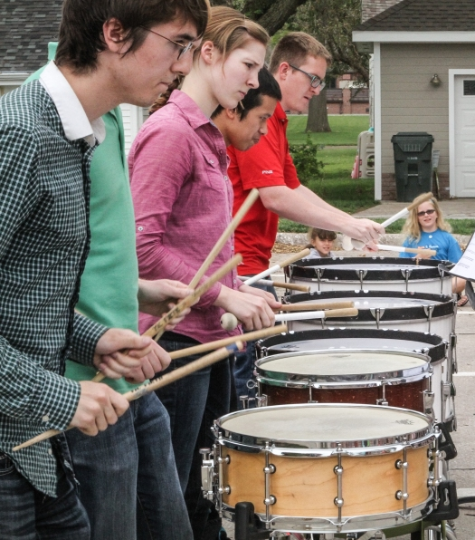 Shyann Harms and Lizzye Wrightson play air drums while percussionists perform.