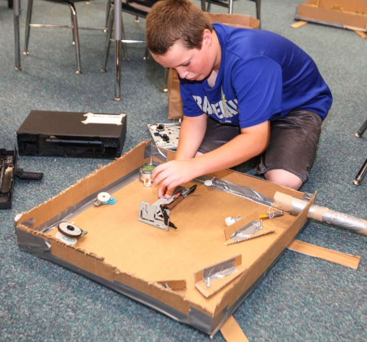 "Alec Cook works on his ""Pin Bug"" pinball machine made from old electronics parts."