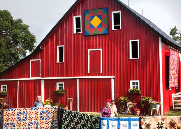 The bright red barn serves as a focal point for quilt and garden displays.