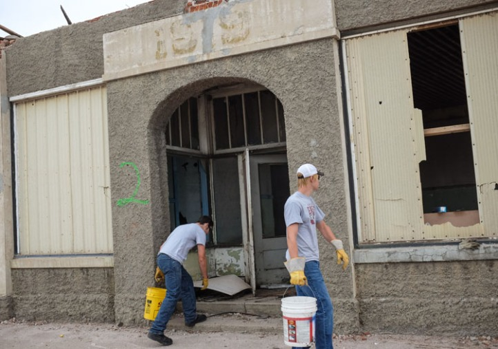 Boys picking up debris in front of the old co-op building.
