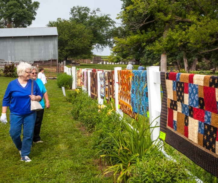 Karen Gingerich and Willa Vesely view quilts displayed on fence railings.