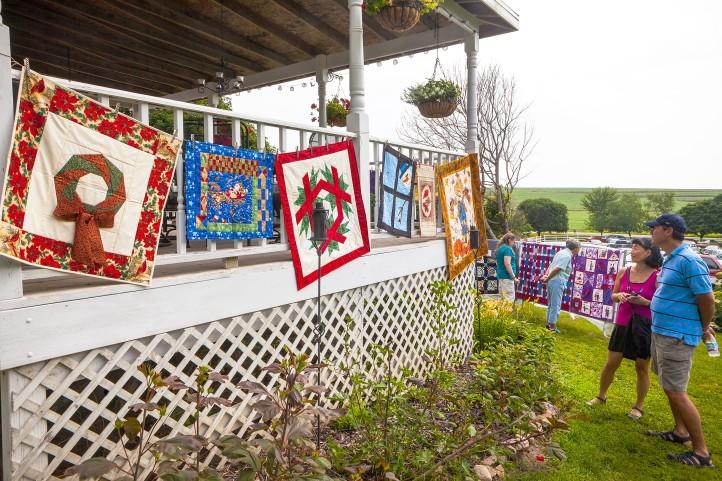 Kim-Jae Kang and husband Jack  Kang view quilts displayed from porch railings.