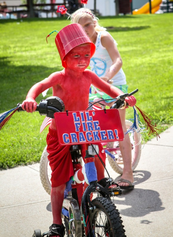 Tyson Soll dressed as a lil' firecracker, rides in the kiddie bike parade.