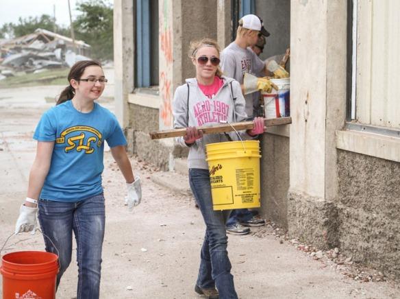 Students carrying bucket loads of debris.