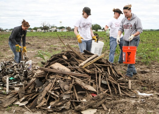 Arlington student Katelyn Ladehoff, left, teahers Ameber Sims and Janelle Lorsch and student Makaela Toebben pile debris in a cornfield east of Pilger.