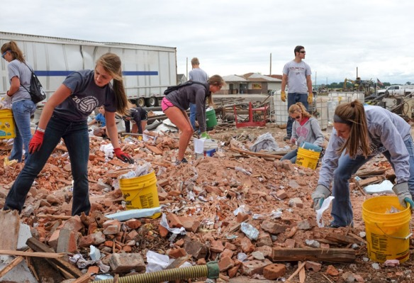 Coaches and students piking up debris.