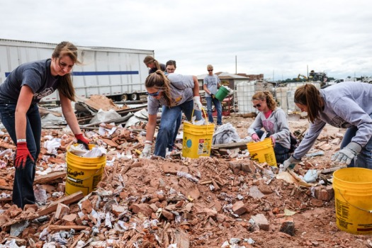 Arlington students. from left, Chloe Lossi, Rachel Brown, teacher Jessica Scott, Abby Hoppe, Sam Plugge, Mine Murphy and teacher Morgan Smmeal pick up paper and other debris Wednesday from an old co-op building that was destroyed in the June 16 tornadoes in Pilger