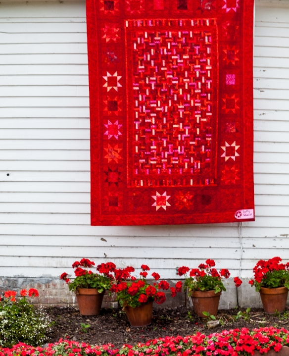 Red geraniums and large red quilt displayed on siding.
