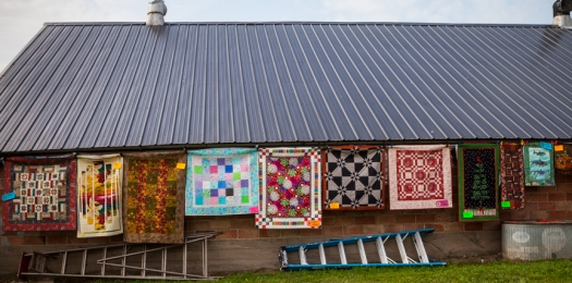 Quilts displayed on the side of a remodeled hog barn.