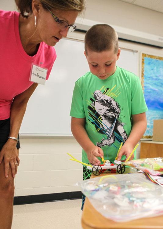 Teacher Mariann Andersen wathes as Rylan Blatter works on his project.