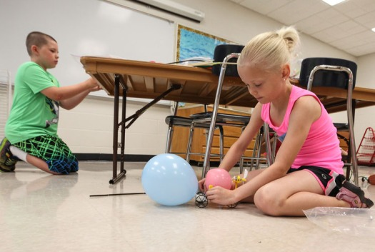 Scarlett Jones attaches a balloon to her mini-vehicle.