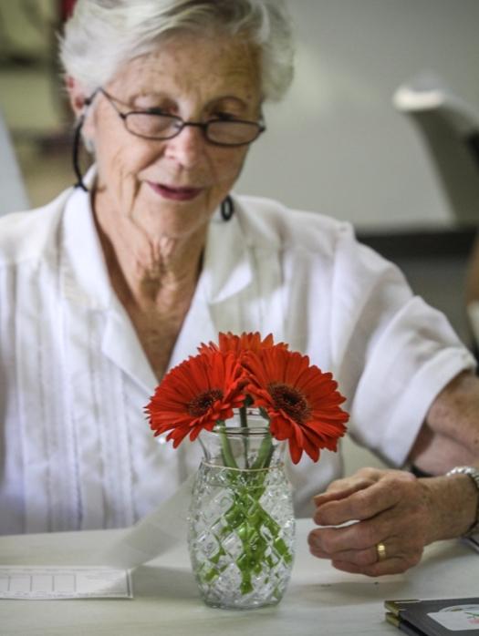 4H Horticulture judge Peg Conley studies a vase of Gerbera daisies