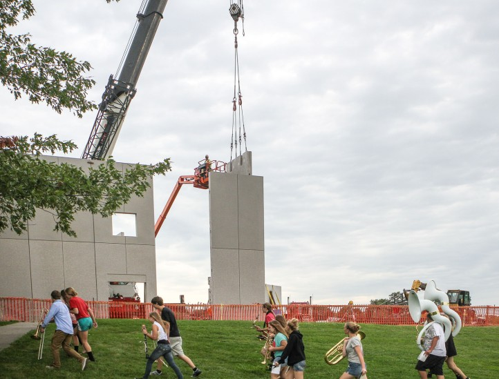 Band members walk to band practice Friday as construction crews erect pre-cast wall panels for the new gym