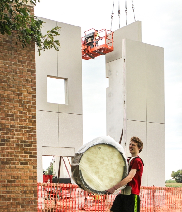 Fort Calhoun percussionist Bradley Lester carries his bass drum to band practice  as crews in thr background  erect pre-cast wall panels for the new gym.